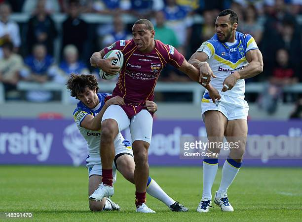 Leroy Cudjoe of Huddersfield is tackled by Stefan Ratchford and Ryan Atkins of Warrington during the Carnegie Challenge Cup Semi Final match between...