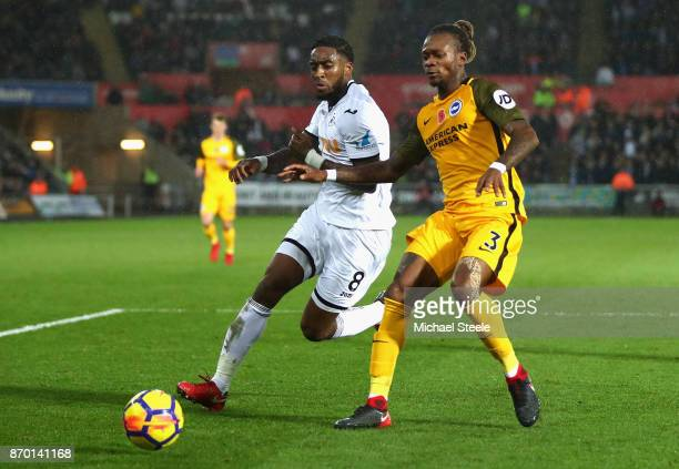 Leroy Fer of Swansea City and Gaetan Bong of Brighton and Hove Albion battle for the ball during the Premier League match between Swansea City and...