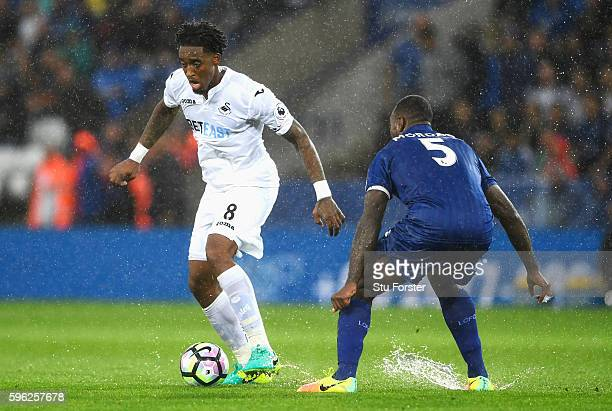 Leroy Fer of Swansea City attempts to take the ball around Wes Morgan of Leicester City during the Premier League match between Leicester City and...