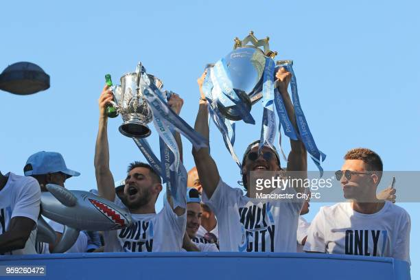 Leroy Sane and Bernardo Silva hold up the trophies during a victory Parade by Manchester City FC on May 14 2018 in Manchester England