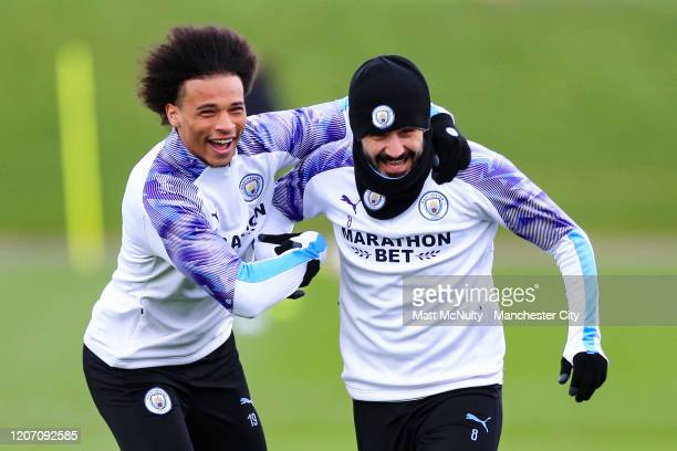 Leroy Sane and Ilkay Gundogan of Manchester City share a joke during the training session at Manchester City Football Academy on February 18 2020 in...