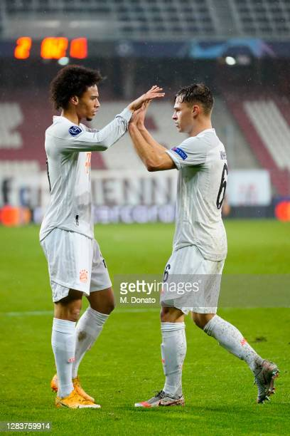Leroy Sane of FC Bayern Muenchen celebrates with team mate Joshua Kimmich after scoring his team's fourth goal during the UEFA Champions League Group...