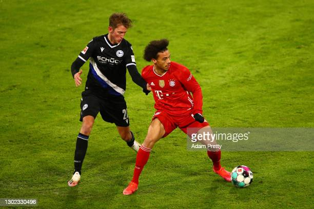 Leroy Sane of FC Bayern Muenchen is challenged by Michel Vlap of Arminia Bielefeld during the Bundesliga match between FC Bayern Muenchen and DSC...