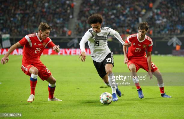 Leroy Sane of Germany is challenged by Aleksandr Erokhin of Russia and Kirill Nababkin of Russia during the International Friendly match between...