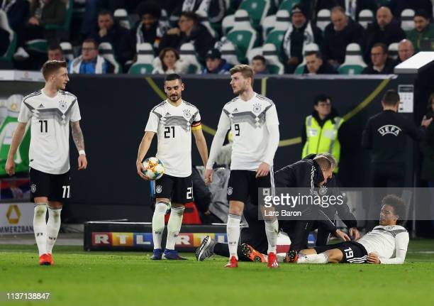 Leroy Sane of Germany receives medical treatment during the International Friendly match between Germany and Serbia at Volkswagen Arena on March 20...