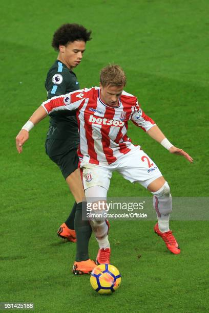 Leroy Sane of Man City battles with Moritz Bauer of Stoke during the Premier League match between Stoke City and Manchester City at the Bet365...