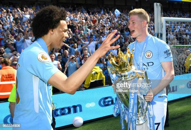 Leroy Sane of Manchester City and Kevin De Bruyne of Manchester City celebrate with The Premier League Trophy after the Premier League match between...