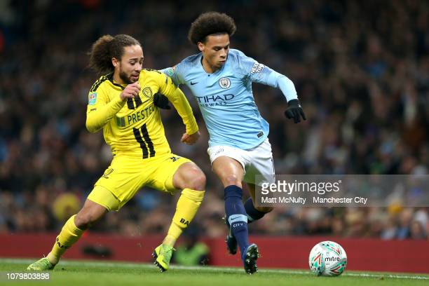 Leroy Sane of Manchester City battles with Marcus Harness of Burton Albion during the Carabao Cup Semi Final First Leg match between Manchester City...