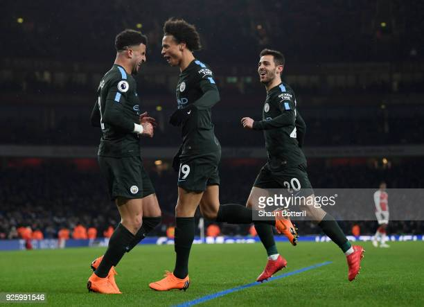Leroy Sane of Manchester City celebrates the third goal with Kyle Walker and Bernardo Silva during the Premier League match between Arsenal and...