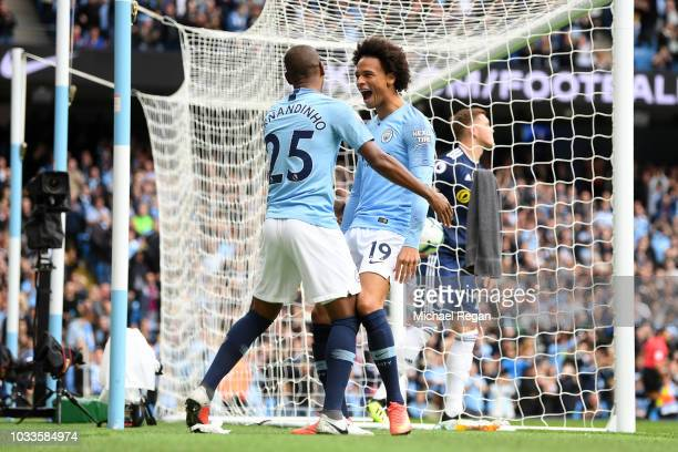 Leroy Sane of Manchester City celebrates with teammate Fernandinho after scoring his team's first goal during the Premier League match between...