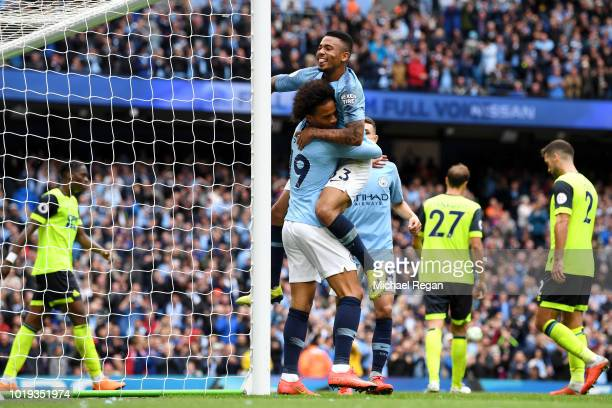 Leroy Sane of Manchester City celebrates with teammate Gabriel Jesus of Manchester City after his shot leads to an own goal from Terence Kongolo of...