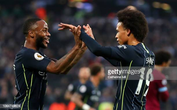 Leroy Sane of Manchester City celebrates with teammate Raheem Sterling after scoring his team's third goal during the Premier League match between...