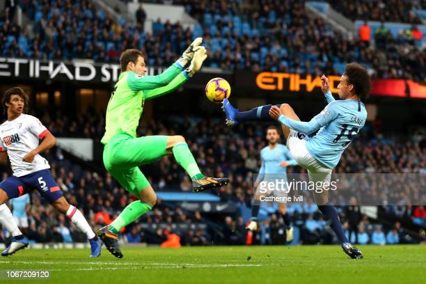 Leroy Sane of Manchester City challenges for the ball with Asmir Begovic of AFC Bournemouth during the Premier League match between Manchester City...