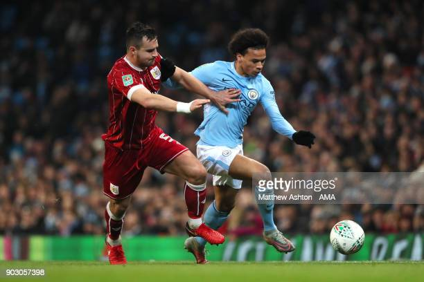 Leroy Sane of Manchester City competes with Bailey Wright of Bristol City during the Carabao Cup SemiFinal first leg match between Manchester City...