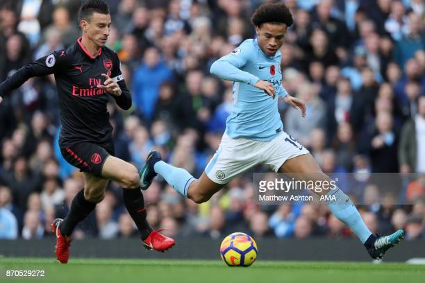 Leroy Sane of Manchester City competes with Laurent Koscielny of Arsenal during the Premier League match between Manchester City and Arsenal at...