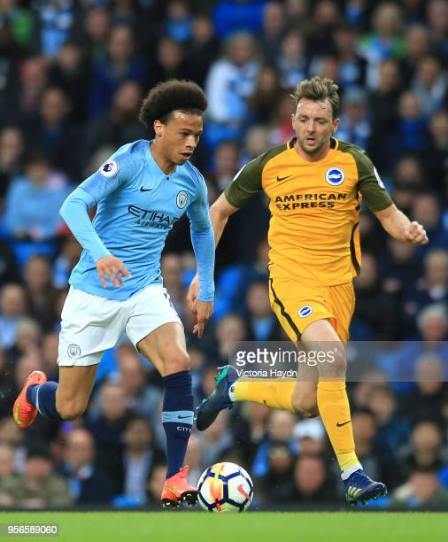 Leroy Sane of Manchester City controls the ball as Dale Stephens of Brighton and Hove Albion chases during the Premier League match between...
