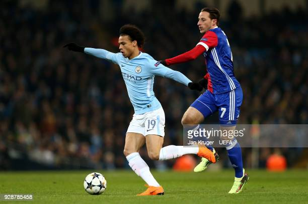 Leroy Sane of Manchester City holds off Luca Zuffi of Basel during the UEFA Champions League Round of 16 Second Leg match between Manchester City and...