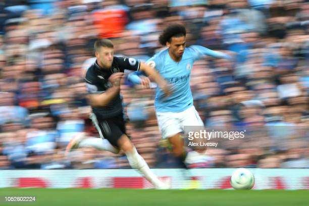 Leroy Sane of Manchester City is challenged by Johann Berg Gudmundsson of Burnley during the Premier League match between Manchester City and Burnley...