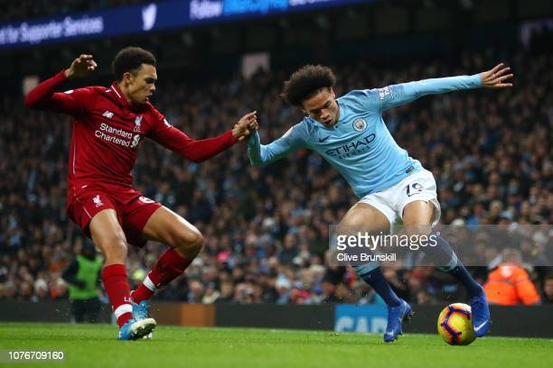 Leroy Sane of Manchester City is challenged by Trent AlexanderArnold of Liverpool during the Premier League match between Manchester City and...