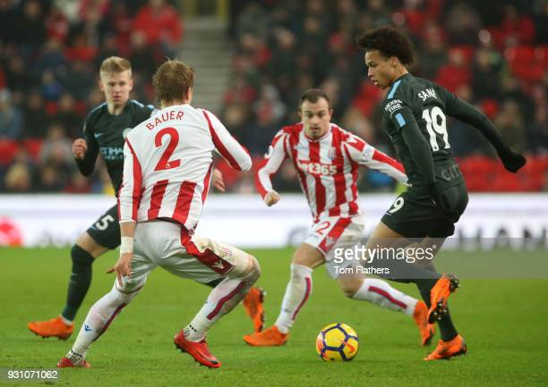Leroy Sane of Manchester City is faced by Moritz Bauer of Stoke City during the Premier League match between Stoke City and Manchester City at Bet365...