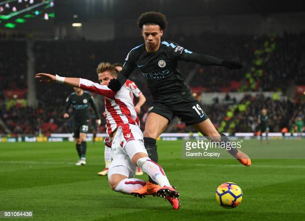 Leroy Sane of Manchester City is tackled by Moritz Bauer of Stoke City during the Premier League match between Stoke City and Manchester City at...
