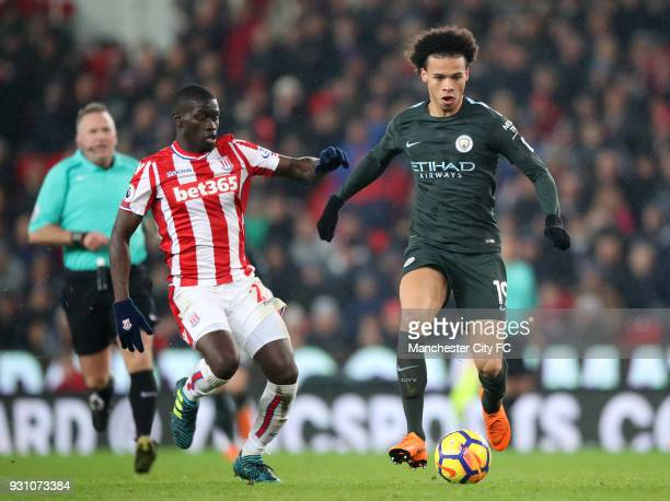 Leroy Sane of Manchester City is watched by Badou Ndiaye of Stoke City during the Premier League match between Stoke City and Manchester City at...