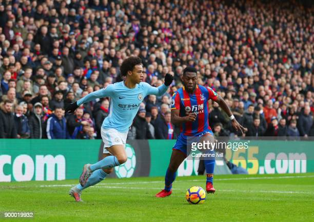 Leroy Sane of Manchester City is watched by Timothy FosuMensah of Crystal Palace during the Premier League match between Crystal Palace and...
