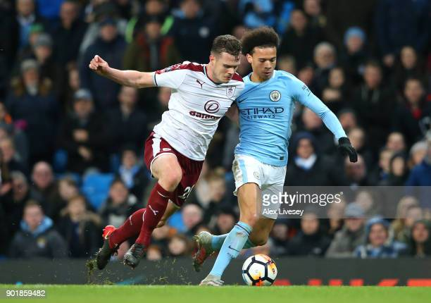 Leroy Sane of Manchester City runs with the ball under pressure from Kevin Long of Burnley during The Emirates FA Cup Third Round match between...