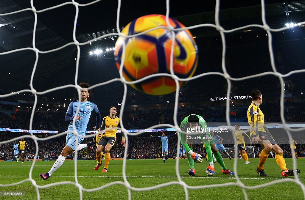 Leroy Sane of Manchester City (L) scores his sides first goal during the Premier League match between Manchester City and Arsenal at the Etihad Stadium on December 18, 2016 in Manchester, England.