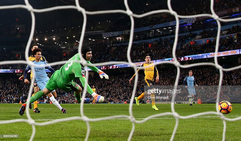 Leroy Sane of Manchester City (L) scores his sides first goal past Petr Cech of Arsenal (C) during the Premier League match between Manchester City and Arsenal at the Etihad Stadium on December 18, 2016 in Manchester, England.