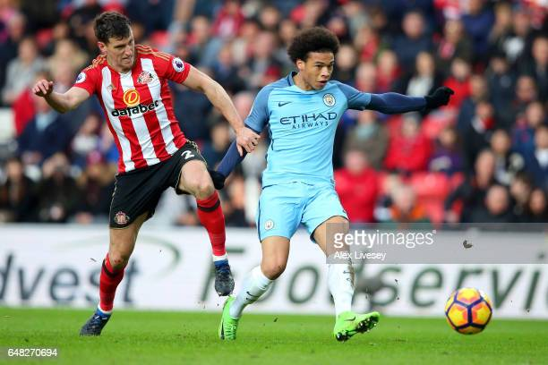 Leroy Sane of Manchester City scores his sides second goal while Billy Jones of Sunderland attempts to stop him during the Premier League match...