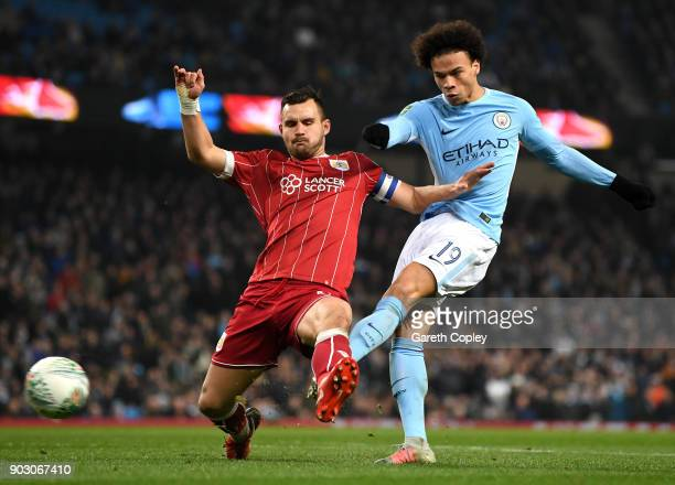 Leroy Sane of Manchester City shoots under pressure from Bailey Wright of Bristol City during the Carabao Cup SemiFinal First Leg match between...