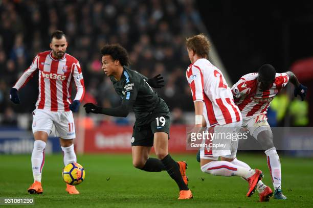 Leroy Sane of Manchester City takes on Jese Moritz Bauer and Badou Ndiaye of Stoke City during the Premier League match between Stoke City and...
