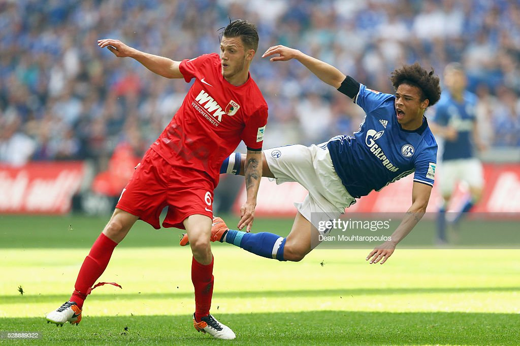 Leroy Sane of Schalke is tackled and stopped by Jeffrey Gouweleeuw of FC Augsburg during the Bundesliga match between FC Schalke 04 and FC Augsburg held at Veltins-Arena on May 7, 2016 in Gelsenkirchen, Germany.