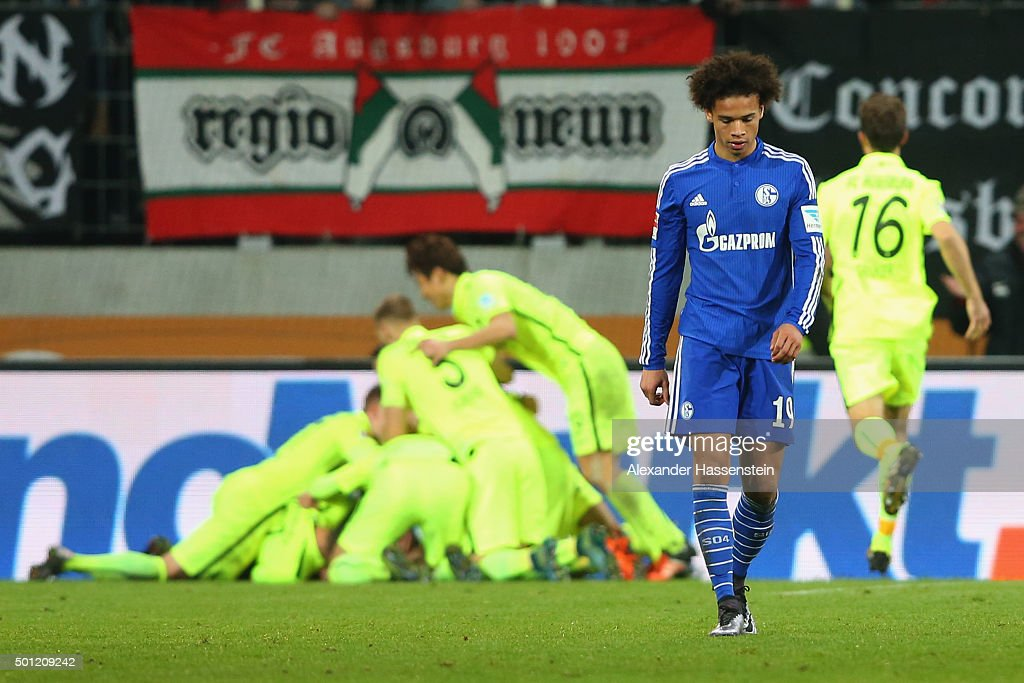 Leroy Sane of Schalke looks dejected whilst players of Augsburg celebrate the winning goal during the Bundesliga match between FC Augsburg and FC Schalke 04 at WWK Arena on December 13, 2015 in Augsburg, Germany.