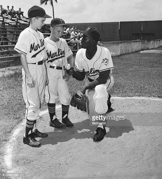 "Leroy ""Satchel"" Paige, relief pitcher for the Miami Marlins of the International League, gives baseball pointers to two young boys dressed in..."