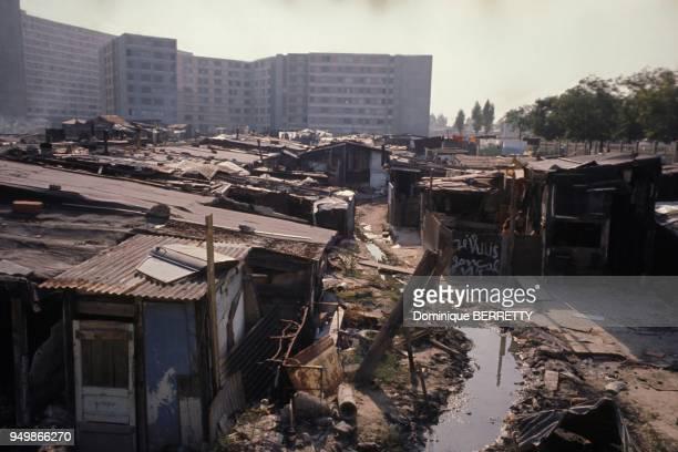 Lers habitations precaires d'un bidonville de la banlieue parisienne, devant de nouveaux immeubles construits afin d'offrir de meilleurs conditions...