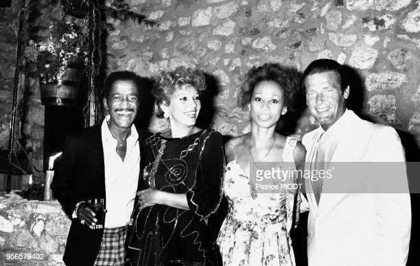 Les acteurs Sammy Davis Junior et Roger Moore accompagnés de leurs femmes assistent à la soirée Piaget le 8 août 1983 à Monaco