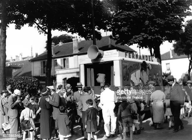 Les badauds regardent passer les voitures suiveuses à l'effigie de Fernandel lors du Tour de France en 1937 en France