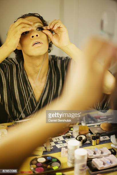 Les Ballets Trockadero de Monte Carlo performer applies a fake eyelash to his eye lid as the troup prepare backstage on September 16 2008 in London...