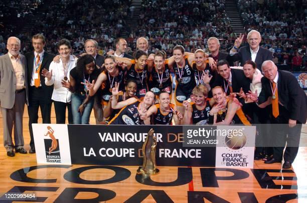 """Les basketteuses de Bourges, leurs entraîneurs et dirigeants, manifestent leur joie en faisant le chiffre """"trois"""", près de leur trophée après leur..."""