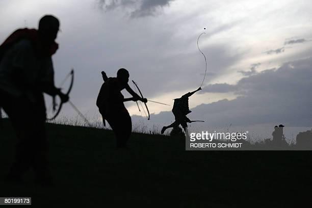 Les batailles codifiees des archers du Trans Mara by Francois Ausseill A Massai warrior releases a stone as other tribe warriors decend a hill as...