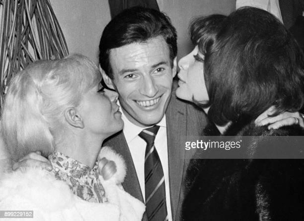 Les chanteuses Isabelle Aubret et Juliette Greco embrassent le 20 décembre 1965 au théâtre Bobino le chanteur Jean Ferrat qui a présenté sur la scène...