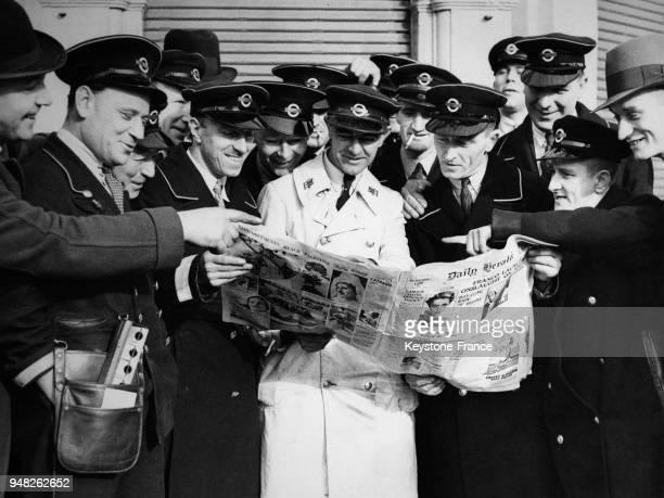 Les chauffeurs de bus en grève lisent le journal devant le garage d'autobus à Londres RoyaumeUni le 7 octobre 1936