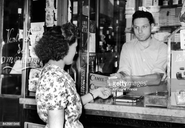 Les cigarettes américaines sont désormais en vente libre : une parisienne achète des cigarettes américaines, des Camel, dans un bureau de tabac à...