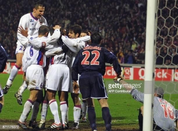 les coéquipiers du Lyonnais Sonny Anderson viennent le féliciter après qu'il ait marqué le 2e but de Lyon sous les yeux du défenseur parisien...