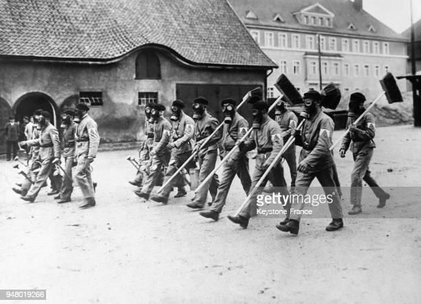 Les employés municipaux munis de masques à gaz et armés de leurs ustensiles défilent dans les rues d'Allenstein PrusseOrientale en juin 1932