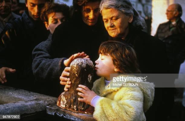 Les fideles viennent se recueillir devant un buste du Christ pendant la fete de Paques ici un enfant embrasse la tete de la statue en 1991 en Albanie