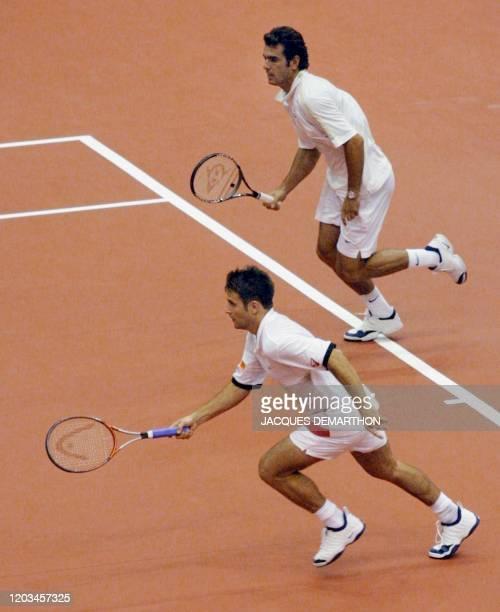 les Français Fabrice Santoro et Cédric Pioline courent vers une balle des Néerlandais Sjeng Schalken et Paul Haarhuis le 22 septembre 2001 au palais...