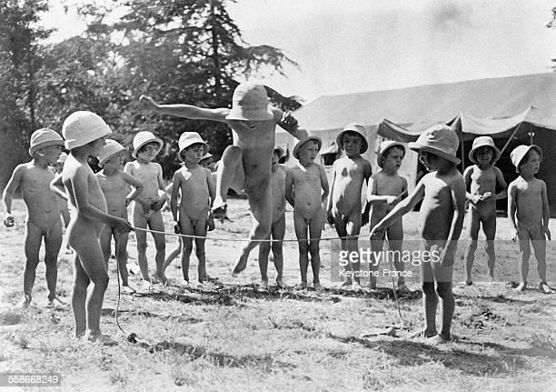 Les élèves de l'école maternelle jouent dehors et sautent à la corde tous nus circa 1930 à Dugny France